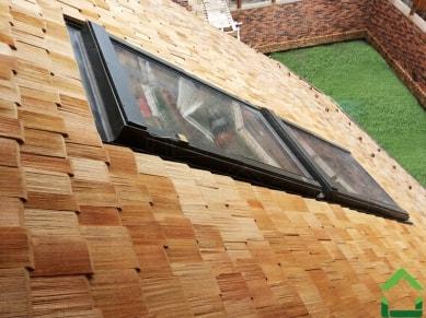 Мансардное окно в деревянной кровле из шинделя